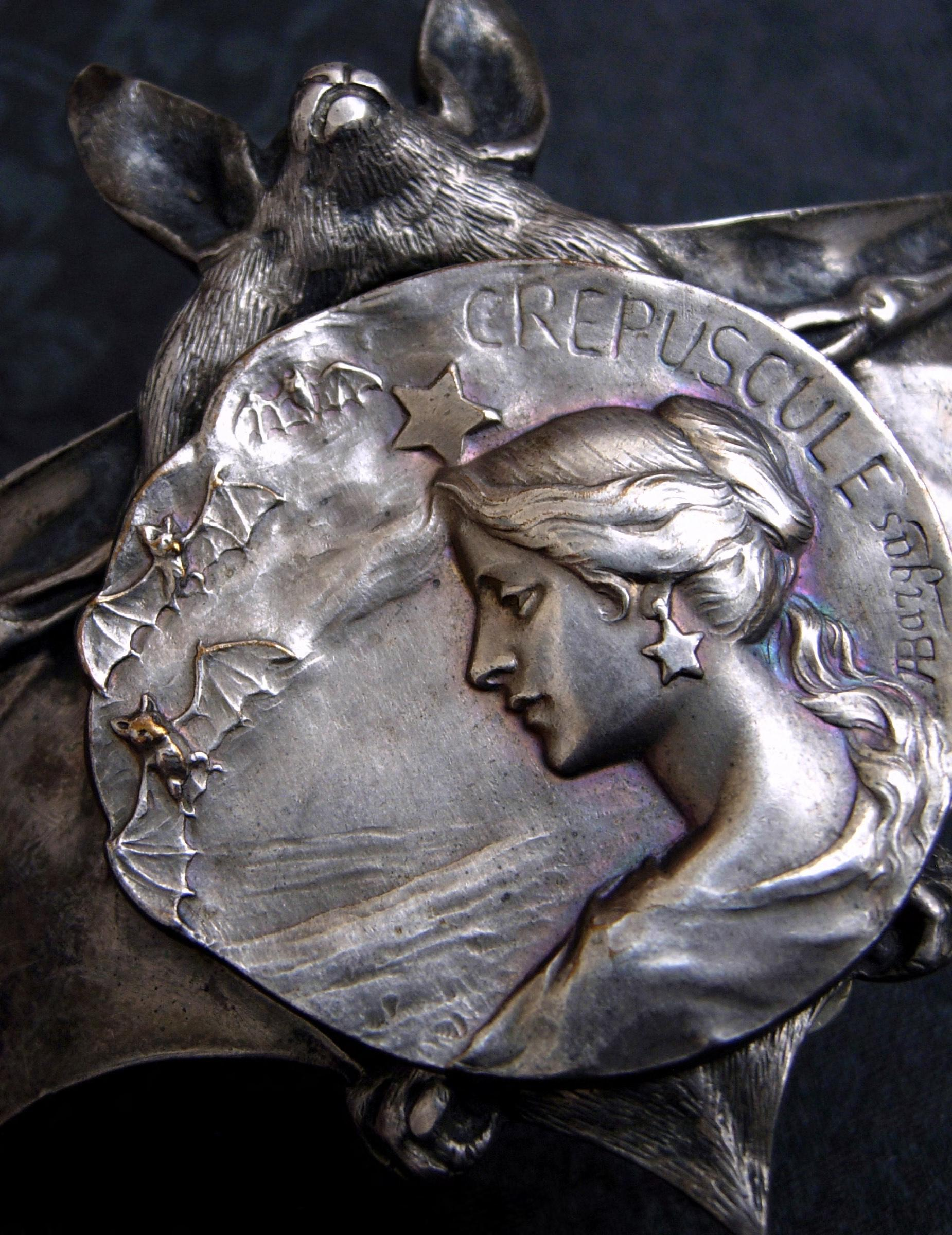 """Crepuscule (French for """"dusk""""): a grand French figural button carved by Armand Bargas with the romantic twilight-themed scene of a chignoned woman surrounded by a trio of bats flying through the starlit sky—resting atop a rare antique Sterling silver buckle carved in the form of an open-winged bat by Ferdinand Erhart, circa 1908."""