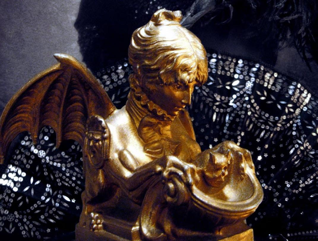 """Self-portrait """"Sphinx"""" inkwell sculpted by legendary actress Sarah Bernhardt, circa 1880. The inkwell portion is topped with a horned skull, and she has comedy-tragedy-mask shoulder epaulettes in tribute to her passion for theater, the body of a transformative griffin with scaled tail, fierce claws, and dramatic batwings ready to take flight—all topped off with a high ruffled collar and impeccably tied ribbon bow around her neck."""