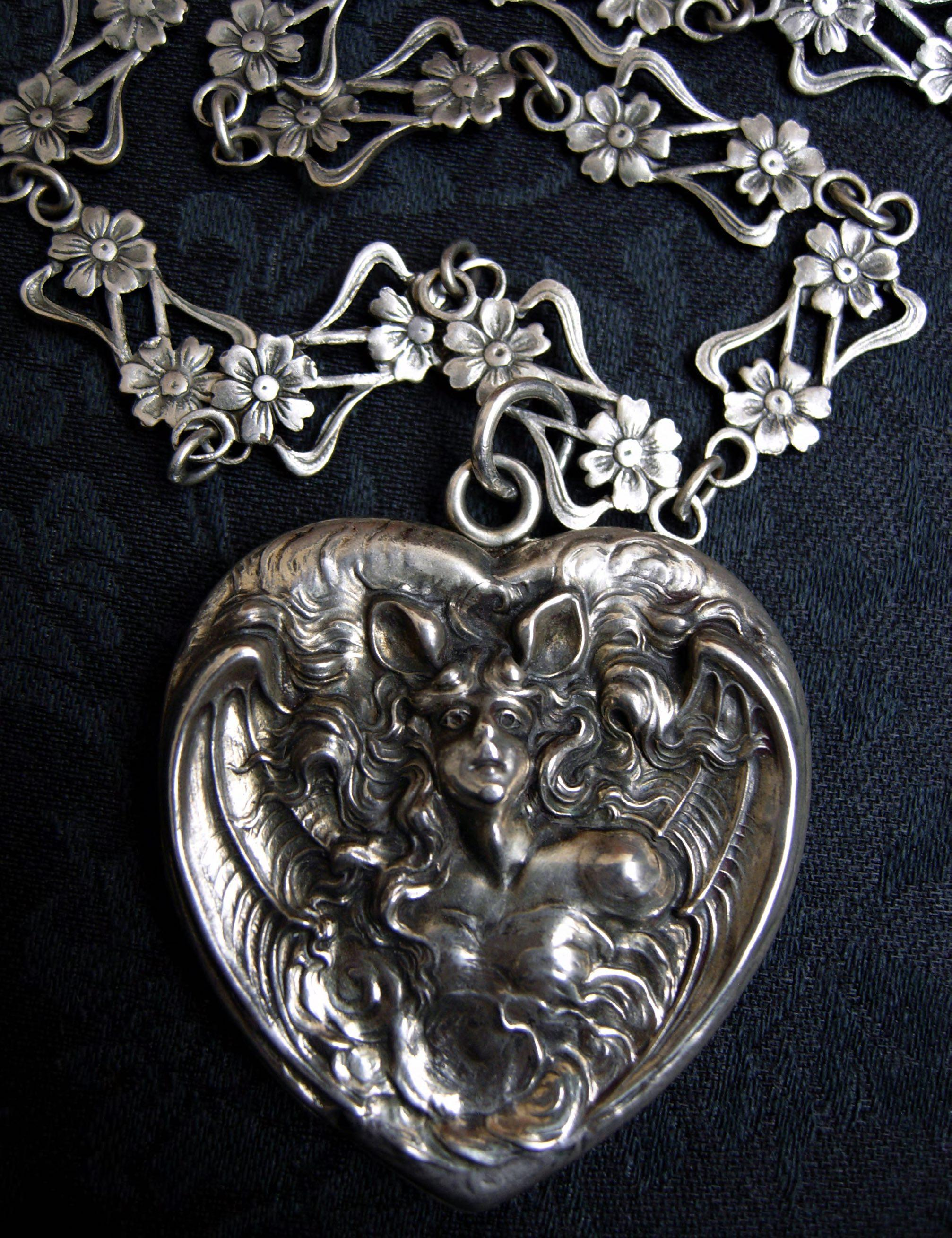 Bat Woman heart-shaped photo locket made by Unger Brothers, paired with a handmade antique silver French Art Nouveau sautoir chain with floral filigree design, circa 1900.